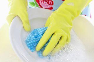 Девушка моет посуду в перчатках